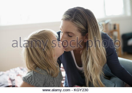 Affectionate blonde mother and toddler daughter kissing - Stock Photo