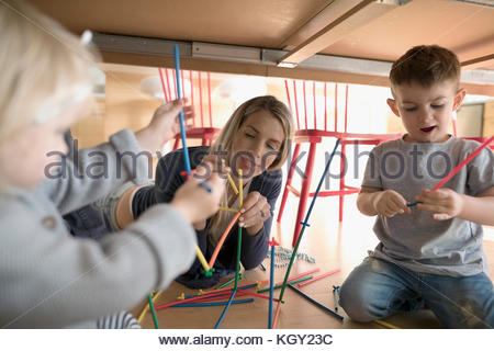 Mother and toddler children playing with connector sticks underneath table - Stock Photo