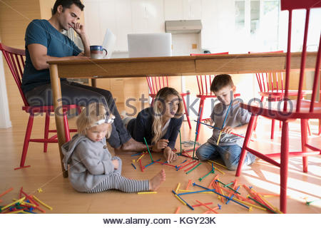 Father working at laptop at table and mother with toddler children playing with connector sticks on floor - Stock Photo