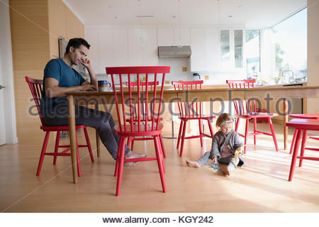 Father working at laptop at table with toddler daughter playing on floor - Stock Photo
