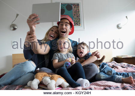 Young family taking selfie with digital tablet on bed - Stock Photo