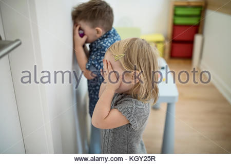 Toddler brother and sister covering eyes, playing hide and seek game - Stock Photo