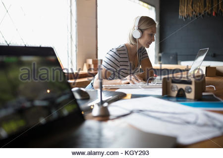 Female designer with headphones listening to music at laptop near virtual reality simulator glasses in office - Stock Photo