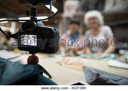 Smiling female fashion designers vlogging with digital camera in workshop - Stock Photo