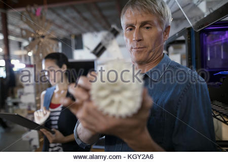Designers with digital tablet examining cog prototype at 3D printer in workshop - Stock Photo