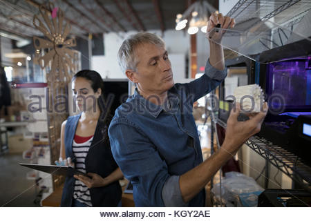 Designers with digital tablet using 3D printer in workshop - Stock Photo