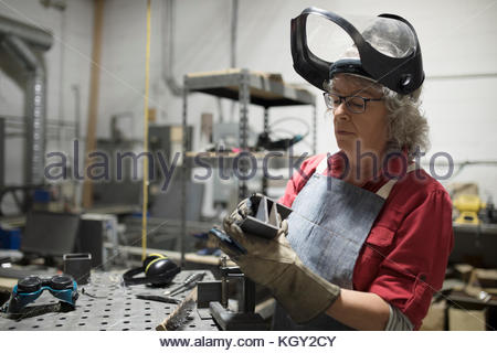 Senior female welder examining steel part in workshop - Stock Photo