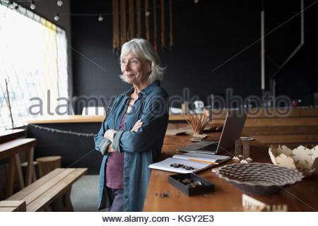 Pensive senior female entrepreneur looking away at laptop - Stock Photo