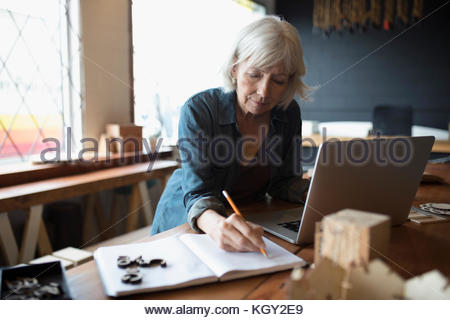 Female senior designer working at laptop, taking notes in notebook - Stock Photo