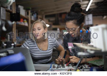 Female engineers using soldering iron on circuit board in workshop - Stock Photo