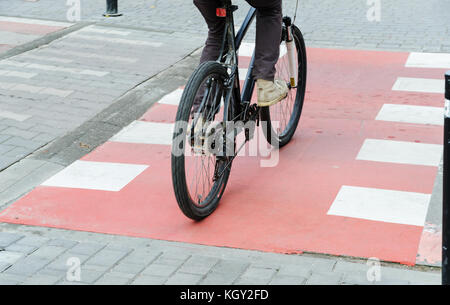 A cyclist on a bicycle is crossing the road on the bicycle path. - Stock Photo