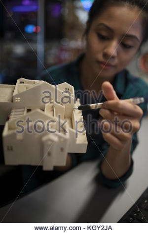 Close up female architect welding architectural model - Stock Photo