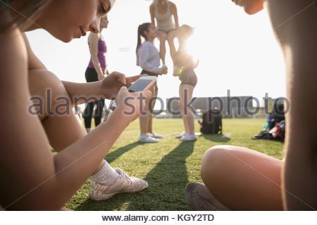 Teenage girl high school cheerleader texting with smart phone on sunny football field - Stock Photo