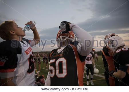 Teenage boy high school football players drinking water on football field sideline - Stock Photo