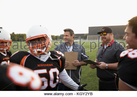 Coaches talking to teenage boy high school football team before game on football field - Stock Photo