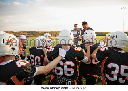 Coaches talking to teenage boy high school football team before game on sunny football field - Stock Photo