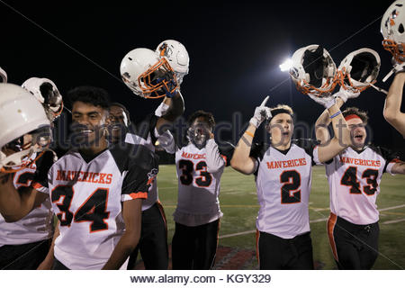 Teenage boy high school football team cheering, celebrating and holding helmets on football field - Stock Photo