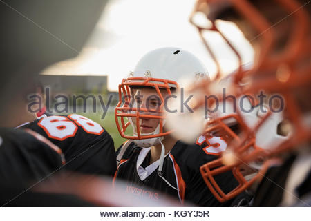 Teenage boy high school football player wearing helmet and sports uniform - Stock Photo