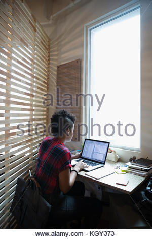 Creative businesswoman using laptop at window in office - Stock Photo