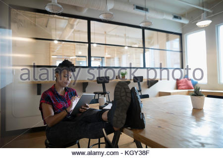 Creative businesswoman using digital tablet with feet up on conference room table - Stock Photo