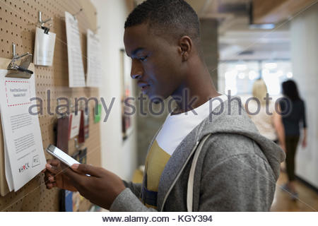 Male freelancer with smart phone checking message board in office - Stock Photo