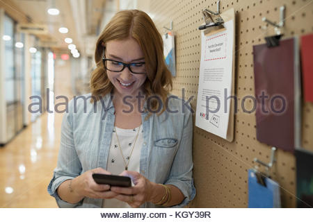 Smiling female freelancer texting with smart phone at message board in office - Stock Photo