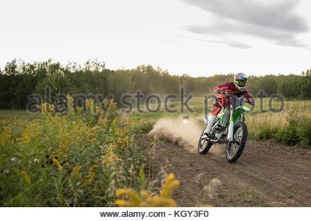 Man racing motorbike on rural dirt road - Stock Photo