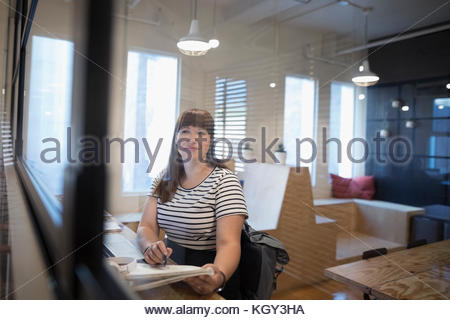 Portrait confident female designer brainstorming, writing in notebook in office - Stock Photo