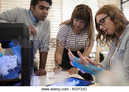 Designers examining glove prototype at 3D printer in office - Stock Photo