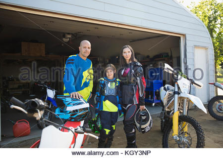 Portrait confident family near motorbikes in driveway - Stock Photo