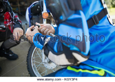 Girl using socket wrench, fixing motorbike - Stock Photo