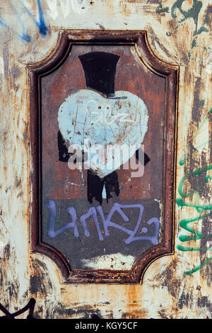 Gentleman wearing top hat - street art drawn on the weathered rusty wall in Camden, London. - Stock Photo