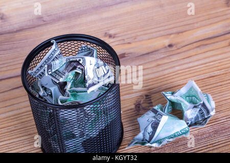 Dollar banknotes crumpled inside garbage basket, rubbish bin focused on consuming money in finance concept, on wooden - Stock Photo