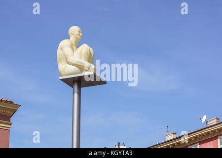 Nice, France 15 August 2017 :A man sitting still and meditating with blue sky background. Glowing statue on the - Stock Photo