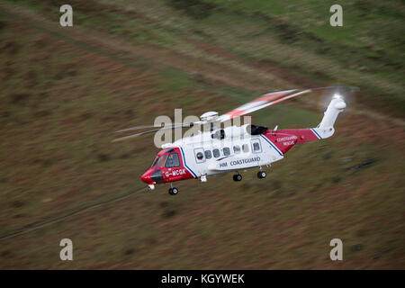 HM Coastguard Search & Rescue Helicopter Rescue 936, conducting low flying training in Snowdonia. - Stock Photo