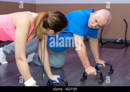 female fitness trainer physiotherapist helping his senior client doing pushups - Stock Photo