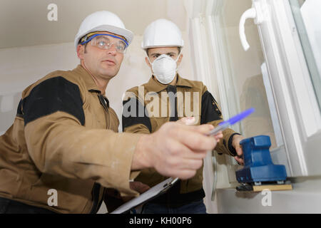 apprentice builder in hardhat sanding wall indoors - Stock Photo
