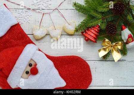 Christmas composition: boots for gifts, decoration fir branch with bright toys, cakes in the form of heart on a - Stock Photo