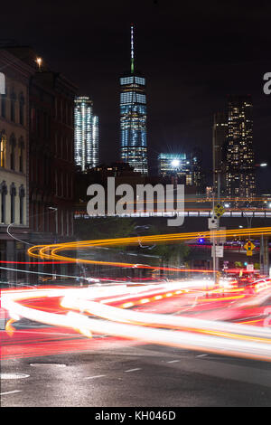 Vehicle lights long exposure on busy Brooklyn Bridge road with One World Trade Centre and Manhattan skyscrapers - Stock Photo