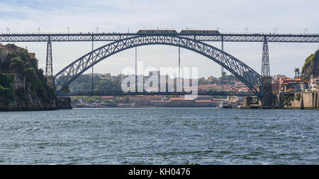 A train passing over Ponte Dom Luís I in Porto as seen from a boat on the Douro River. - Stock Photo