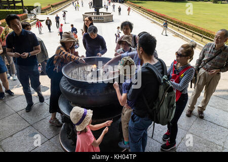 Nara, Japan -  May 29, 2017: Tourist are lighting incense in front of hte Great Buddha Hall part of the buddhist - Stock Photo