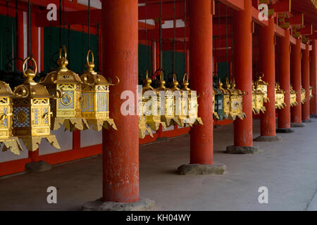 Nara - Japan, May 29, 2017: Row of gold plated lanterns at the Kasuga Taisha shrine - Stock Photo