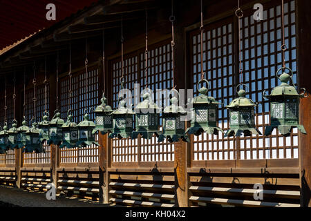 Nara - Japan, May 29, 2017: Row of bronze lanterns at the Kasuga Taisha shrine - Stock Photo
