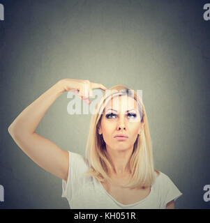 Portrait of a thinking woman bewildered scratching her head seeks a solution looking up isolated on gray wall background. - Stock Photo