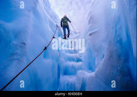 Woman walking steps out of a ice cave in Fox Glacier, South Island, New Zealand - Stock Photo