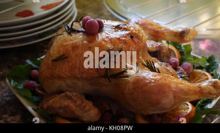 Closeup view of roasted chicken on white plate on kitchen table. - Stock Photo