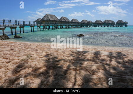 Tropical lagoon with overwater bungalows of a resort seen from a sandy beach with shade of trees, Tikehau, Tuamotus, - Stock Photo