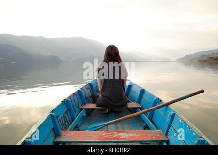 girl on a boat in the middle of pokhara lakeside nepal - Stock Photo