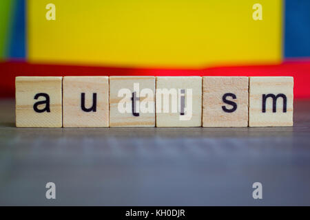 Autism word on wood cubes on table against colorful background - Stock Photo