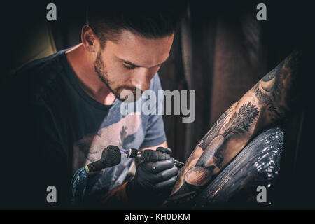 Professional tattoo artist makes a tattoo on a young man's hand - Stock Photo